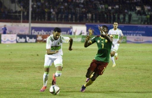 © AFP | La star de l'Algérie Ryad Mahrez à la lutte avec Toko Ekambi du Cameroun en qualifications au Mondial-2018, le 9 octobre 2016.