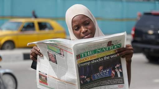 """Une femme musulmane lisant un journal qui titre """"Trump choque le monde"""", à Lagos, au Nigeria"""
