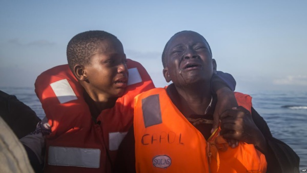 """""""une fille de 11 ans du Nigeria (à gauche), qui m'a dit que sa mère est morte en Libye, pleure à côté de son frère de 10 ans à bord d'un bateau de sauvetage d'une ONG. Les enfants ont navigué pendant des heures dans un bateau en caoutchouc surchargé avec d'autres réfugiés lors d'une opération de sauvetage sur la Méditerranée, à environ 23 kilomètres au nord de Sabratha, en Libye"""""""