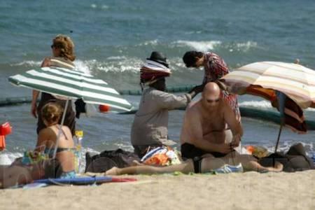 Les vendeurs de serviettes, chapeaux, lunettes de soleil jouent à cache-cache avec la police.