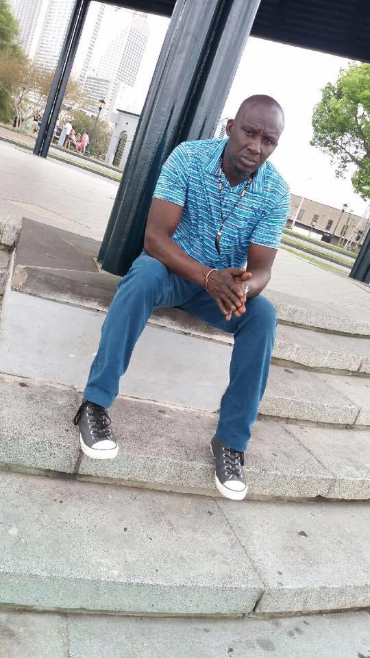 Assane Diouf portait des jeans noirs et un t-shirt bleu, à son arrivée à l'aéroport de Dakar