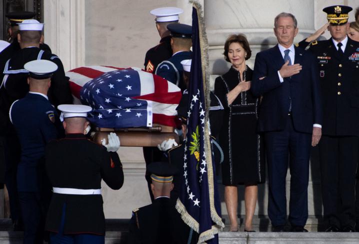 L'ancien président américain George W. Bush et son épouse Laura se recueillent à l'arrivée du cercueil de George H. W. Bush au Capitole, le 3 décembre 2018 / AFP