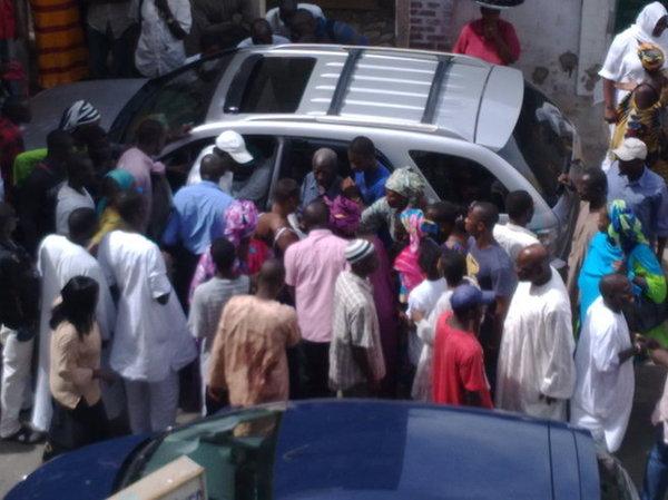 La voiture de la dame , entourée par une foule monstre