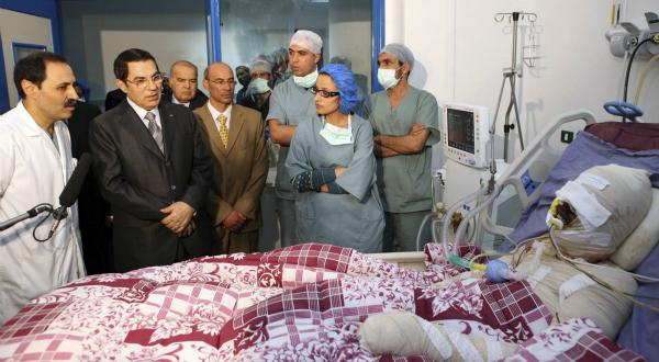 1. L'ancien président tunisien Zine el-Abidine Ben Ali pose à côté de Mohamed Bouazizi, le 28 décembre 2010, à l'hopital de Ben Arous, près de Tunis. Il tente ainsi d'afficher son soutien afin d'apaiser le mouvement de protestation qui est né de l'immolation par le feu de ce jeune homme, décédé quelques jours plus tard, le 4 janvier 2011. REUTERS/Présidence tunisienne.