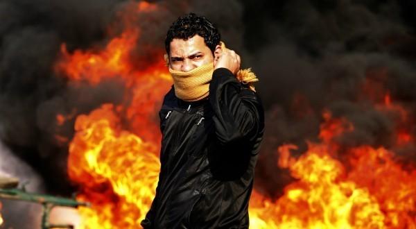 2. Un manifestant au Caire, devant une barricade en flammes, le 28 janvier 2011, au quatrième jour de heurts violents avec la police où des dizaines de milliers de manifestants égyptiens ont réclamé le démission d'Hosni Moubarak, en place depuis trente ans. REUTERS/Goran Tomasevic.
