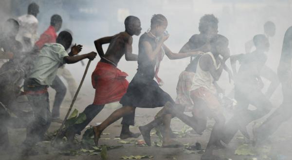 10. Des manifestants de l'opposition (pour le parti de Tshisekedi, l'Union pour la démocratie et le progrès social) courent à travers un nuage de gaz lacrymogène, le 26 novembre, près de l'aéroport de Kinshasa. REUTERS/Finbarr O'Reilly.