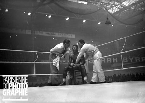 Guerre 1939-1945. Assane Diouf, boxeur français, conseillé par ses soigneurs, lors de son match contre Jean Despeaux. Paris, palais des sports, avril 1941.