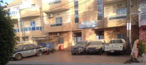 Cimetière de voitures devant un bâtiment officiel - Cela se passe au Sénégal !