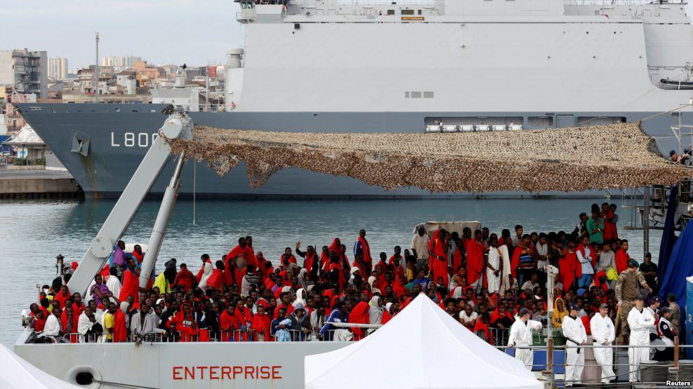 Des migrants attendent pour descendre du bateau de la Royal Navy Ship HMS Enterprise dans un port sicilien, Italie, le 23 octobre 2016.