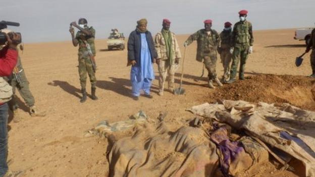 Des soldats nigériens devant les cadavres de migrants abandonnés dans le désert