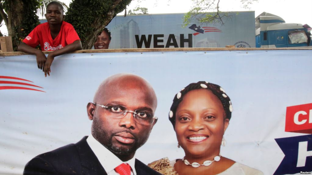 Un partisan de l'ancien footballeur et candidat à la présidence du Congrès pour le changement démocratique (CDC) George Weah se tient derrière une bannière de la campagne présidentielle à Monrovia, Libéria, le 6 octobre 2017.