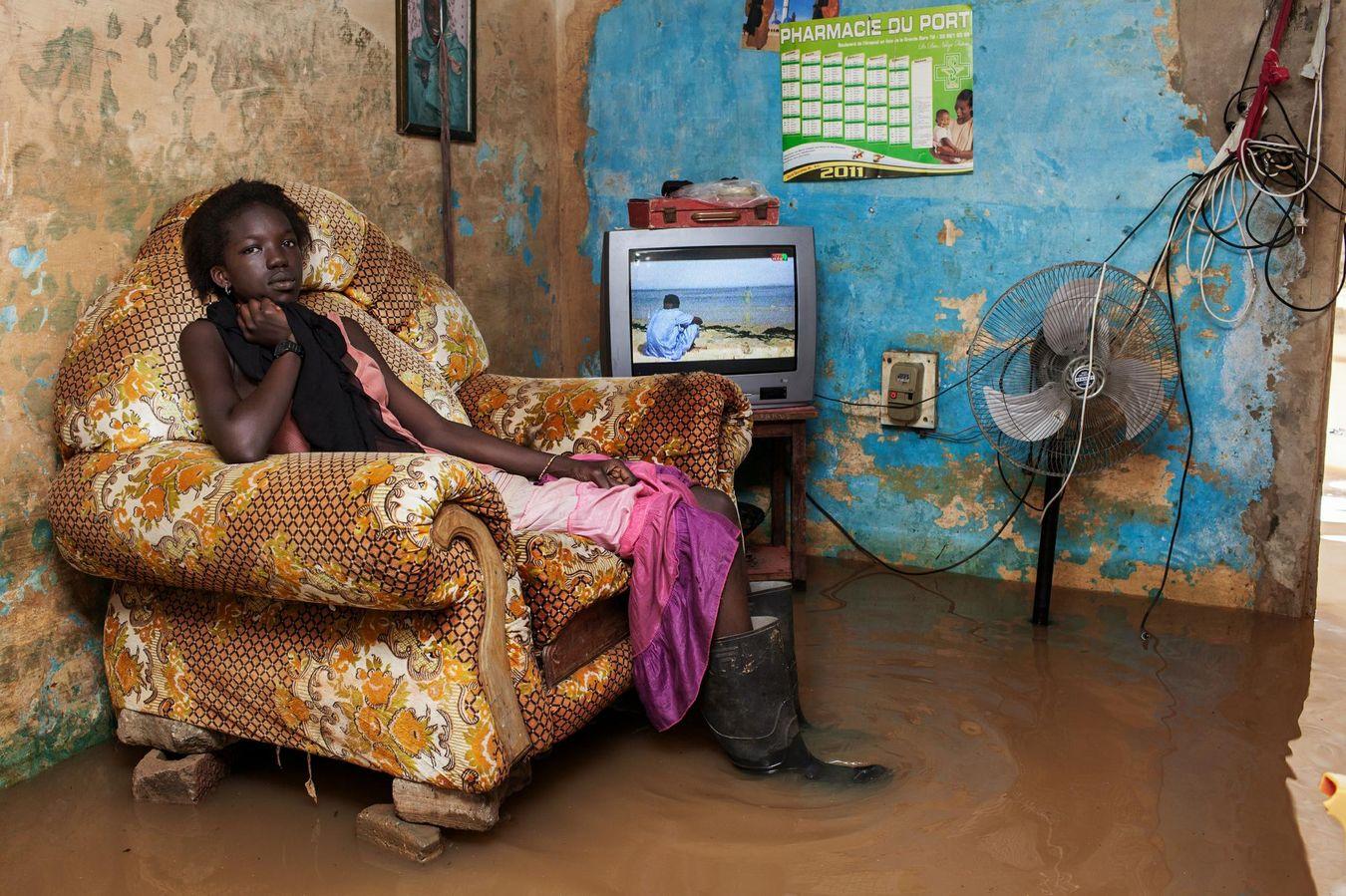 Chaussée de bottes en caoutchouc, Fanta, 18 ans, une habitante de Thiaroye, attend patiemment que l'eau se retire. A la recherche d'un travail, ils sont de plus en plus nombreux à quitter la campagne et à venir s'installer à la périphérie de la capitale.