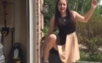 La caméra filme cette fille devant le garage lorsqu'elle fait soudain ça avec ses jambes! Impressionnant!