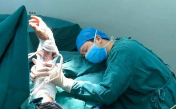 Arrêt sur image - Exténué, un chirurgien s'endort en tenant le bras de son patient